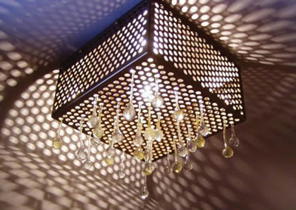 A decorative perforated sheet lampshade, several crystal decoration and the shadow of the lamp on the wall.