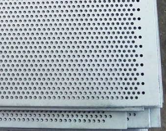There are several mild carbon steel perforated sheets stacked up and down on the ground, their perforated holes are small.