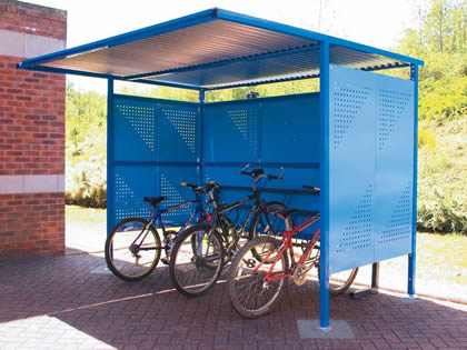 A perforated sunshade shelter and three bicycle is placed under the shelter.