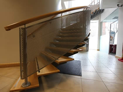 A piece of protective perforated sheet is installed on the spiral stair balustrade.
